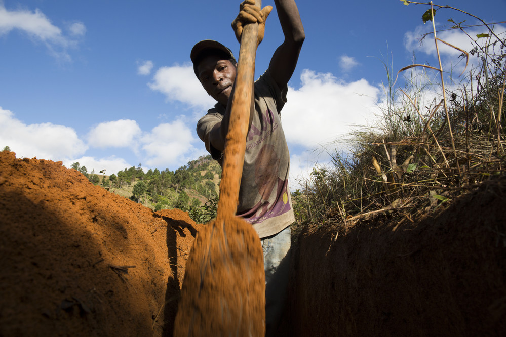 """I am really happy to do it because I want to see my children drinking safe water ."" Richard, 34 years-old father, digging trenches to lay the pipes for a new water facilitation in Belavabary commune."