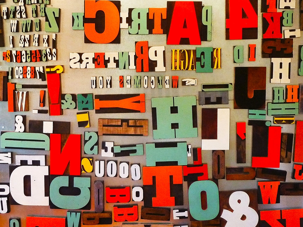 A wall of wood type in the visitors' lounge. The letters are attached magnetically and can be arranged to make personal messages, albeit backwards.