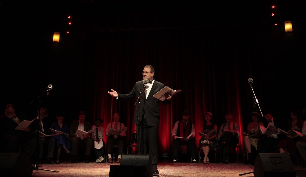 """Fake Radio's Artistic Director David Koff thanks the crowd during curtain call of Fake Radio's performance of """"It's a Wonderful Life"""" at the Alberta Rose Theater"""