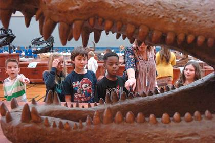 Looking at the mouth of a prehistoric alligator are Tyler Chancler, Baylie Cole, CJ McCabe-Green, J'tavon Ferguson, 2 nd  grade teacher Debbie Allred, and Kylie Crawford.