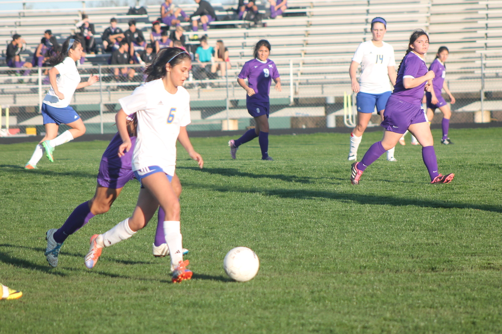 (Photo by Maddie Routon) Daisey Rangel (6) pushes the ball up the field against Bonham.