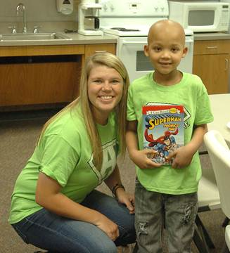 Pantherette Erin Scholl gives Aiden Walters a Superman book that her little brother, Logan, got for him.