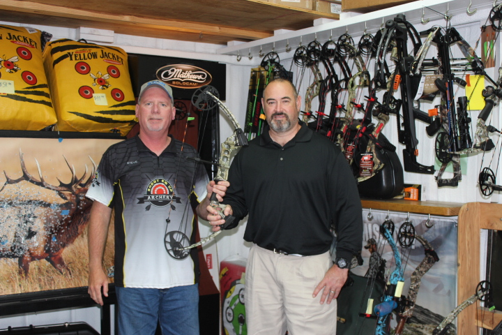 Owner of Shoot Em Up archery Steve Story (left) donates a bow to David Pasternak. Bow to be given to a student in the outdoor education program at North Lamar.