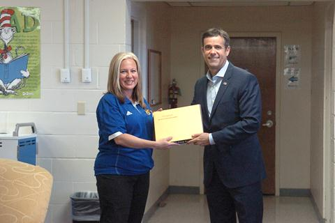 Stone Middle School Principal Kelli Stewart accepts a United State flag from Congress John Ratcliffe that flew over the State Capital in honor of Stone Middle School.