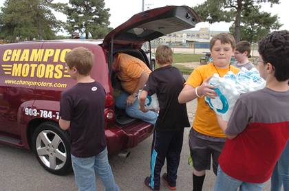 Handing cases of water to Rickey Richardson as he loads the back of his car are, from left, Carson Jones, Caleb Young, Texas Darby, and Donato Curvino.