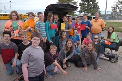 North Lamar middle school students gathered to load the back of a Champion Motor's car driven by Ricky Richardson with relief items for Van, Texas. Kneeling from left are Donato Curvino, Caleb Young, Parker Brown, Carson Jones, Ellie Ables, Hannah Gibbons, Hannah Crosswhite, Jaycie Hall, Hunter Kruger, Avery Cole, and teacher Kenda Felker.  In back are Breanna McConnell, Texas Darby, Brenton Walton, Elena Covington, Emma Fowler, Karsyn Iltis, Candace Bateman, Kevin Dyck, Jake Blackburn, and Richardson.