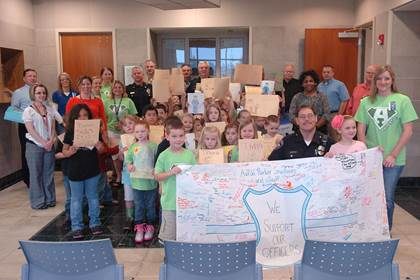 Parker kindergarten students, their teachers and principal filled the foyer of the Paris Police Department to deliver cards, cake, and an appreciation banner to the law enforcement officials.