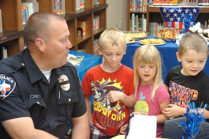 North Lamar School Resource Officer Jeff Akard is a friendly and recognizable face among those in the district.  Brenden Maye, Caitlyn Whitt, and Kason Walker hand Akard a goodie bag made by their class.