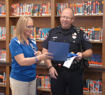 Aaron Parker Principal Tammie Bates shares thank you letters written by students with NL Resource Officer Mike Boaz.