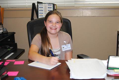 Wearing her 'Principal' badge and sitting behind the desk of Aaron Parker Principal Tammie Bates, Hannah Jackson begins her morning by making notes for announcements and acknowledging student birthdays.