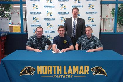 Trevor Burns, center, with Petty Officer Sam Money, left, Petty Officer Christopher Gault, right, and NLHS Principal Clint Hildreth, standing.