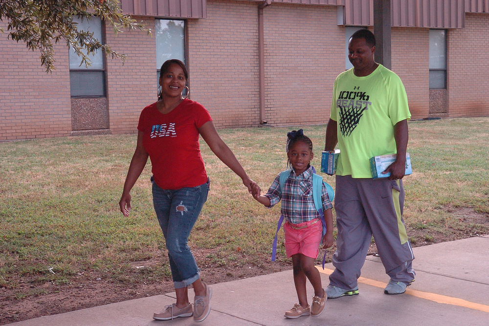 Dressed in her new school clothes, Higgins kindergarten student, Madison Reed, brings her parents, Tamekia and Ronald, along on her first day of school.