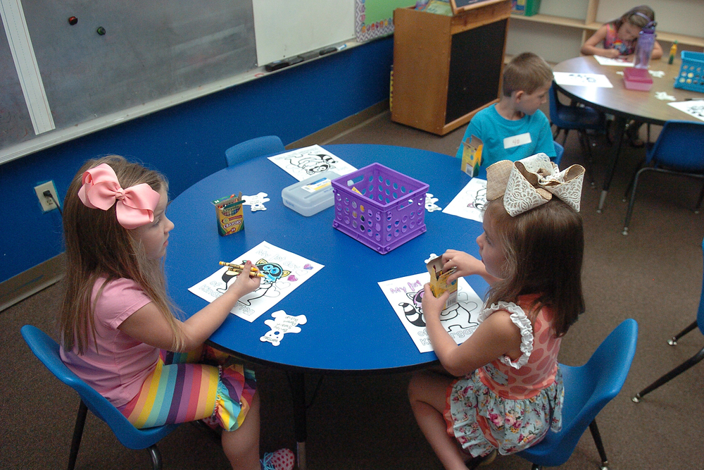 Coloring is an ice breaker when meeting new friends.  From left are Briley Swain, Ellah Kelley, and Patrick Griffith from Morgan Watson's kindergarten class at Higgins Elementary