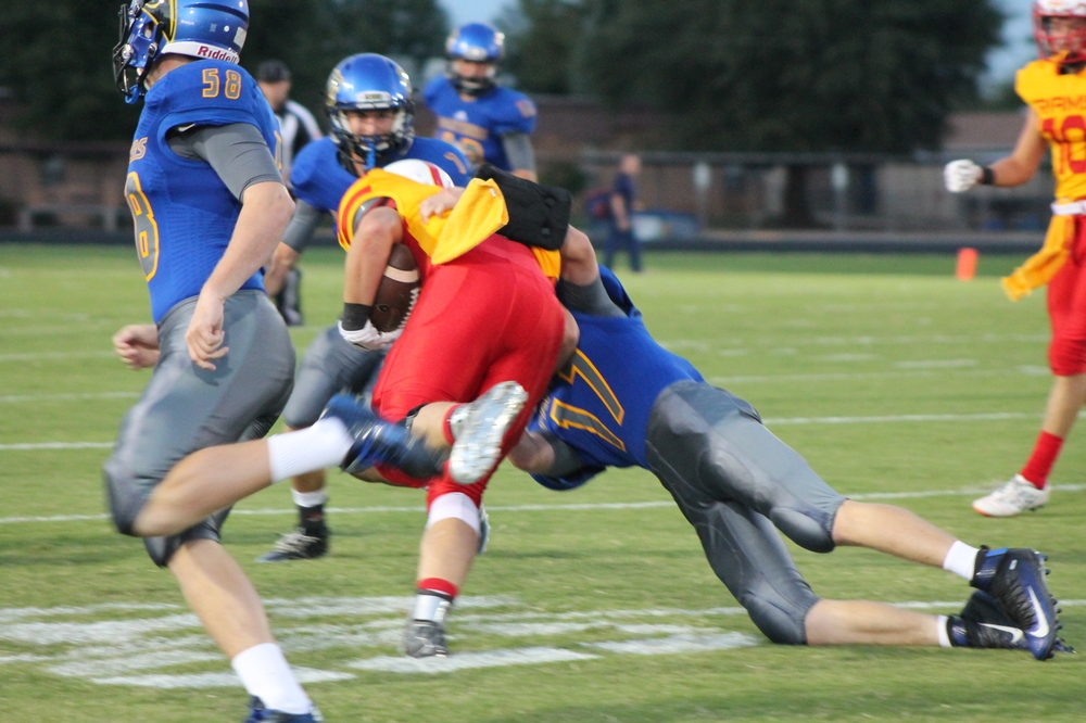 (Photo by Adam Routon) Tyler Biard (17) making a tackle for North Lamar against S&S as Klayton drake (58) looks on.