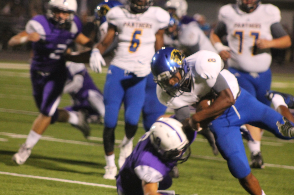 (photo by Maddy Routon) Tyler Hill (8) running through a tackle Friday night.