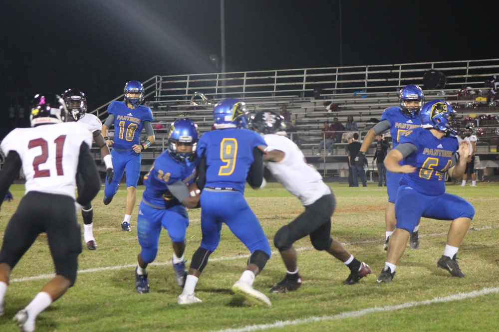 (Photo by Adam Routon) Javon Franklin (24) running through a block set by Menderiz Gray (9) Thursday night.