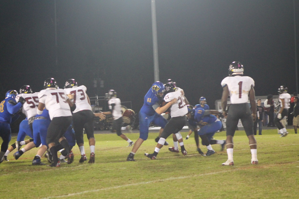 (Photo by Adam Routon) North Lamar's defense making a play on the LE running back.