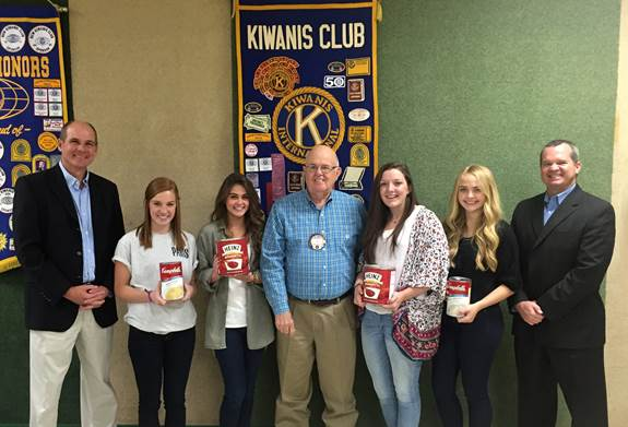With cans in hand at the Kiwanis lunch meeting from left are Paris ISD superintendent Paul Jones, PHS Key Club officers Anna Grace Thrasher and Sloan Clay, Kiwanis Club president Don Dickerson, NLHS Key Club officers Michaela Smith and Katie Kilcrease, and North Lamar ISD superintendent John McCullough. The Crosstown Showdown food drive between Paris and North Lamar is all about helping the community