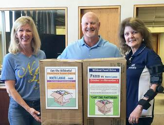 Public Information Officers, Carla Coleman of NLISD (left), and Jeanne Kraft of PISD (right), tape on posters to collection boxes for Bill Coleman of Liberty National Bank.