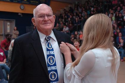 Air Force veteran Norman Davis receives a pin by a North Lamar Beta Club member as the band and choir perform   Salute to the Armed Forces  .
