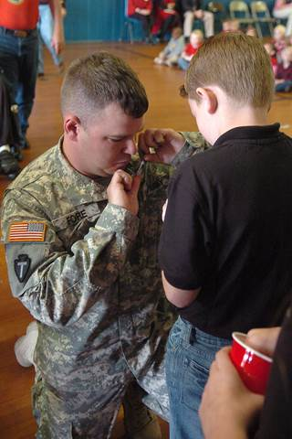 Johnathon Fore gets down on his knees so his son, Caden, can place a pin on his lapel.  The 4th grader, a member of the Student Council and the National Elementary Honor Society, took part in honoring all active and retired members of the Armed Forces.