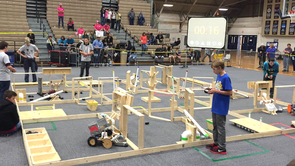 Caleb Young operates the control for Stone's robot guiding it through a maze and performing specific operations as Rustin Shelton (sitting left in black) acts as a spotter helping guide the robot.