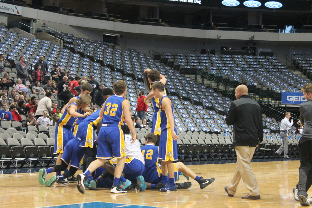 (Photo by Amanda Posey) North Lamar players tackle Menderiz Gray after he tips in the game winning shot against Melissa.
