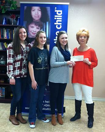 Presenting a check for $1,100 to Rose Kernell, right, of CASA for Kids are North Lamar High School National Honor Society members, from left, Michaela Smith, Brittany Pilkington, and Brittany Birch.