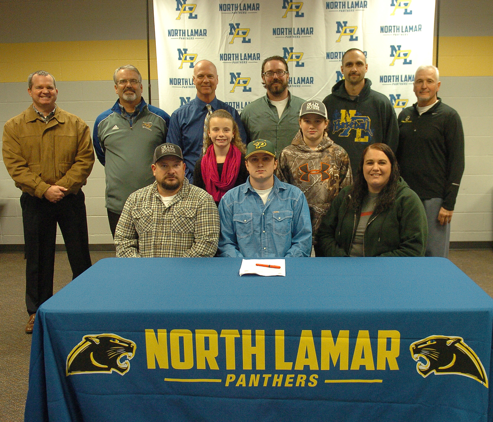 North Lamar's  Hunter Reeves , seated center, is joined by others as he signs to play baseball for the PJC Dragons. Seated with him are parents, Cody and Dana Reeves, along with siblings, Maddie and Gage, directly behind.  Standing in back are NLISD Superintendent John McCullough, NL Head Baseball Coach Scott Igleheart, PJC Head Baseball Coach Deron Clark, PJC Assistant Coach Clay Cox, NL Assistant Coach Chad Chalupa, and NL Athletic Director Tim Billings.