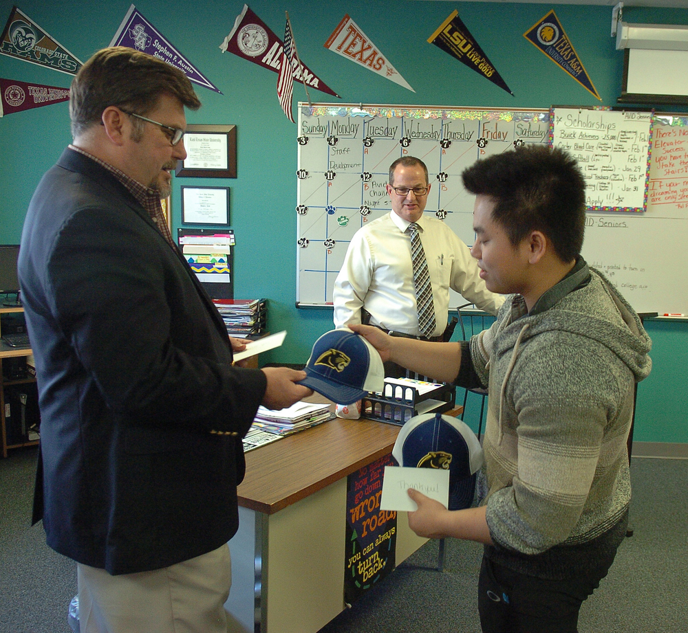 On behalf of Tiffany Page's AVID class, Eric Pheng, right, presents North Lamar Panther ball caps to Gary Young, left, and Chris Bean, center, for talking to them about career options.