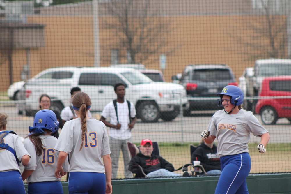 Bill Jones being greeted by her teammates after a three-run homer against Melissa