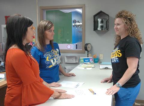 Higgins Elementary Principal Claudia Pursifull, left, and Secretary Melissa Harris, center, assist Cassidy Emeyabbi as she pre-registers her youngest child for next year's kindergarten class.