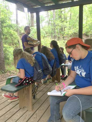 In an outdoor classroom at Sky Ranch, North Lamar fifth graders take notes on the physical structure and function of an alligator.