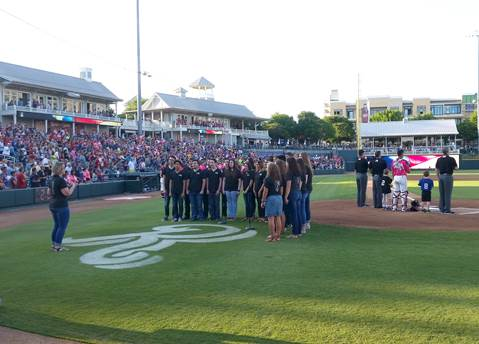 North Lamar High School Choir Director Rebecca Hildreth directs members of the Chamber Singers as they sing the national anthem before the first pitch of the Frisco Roughriders baseball game.