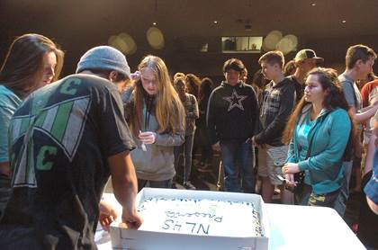 A Shrek cake is cut and served by seniors Sarah Serrano and Nic Corpus to students attending the Theatre Department's reveal party at North Lamar High School.