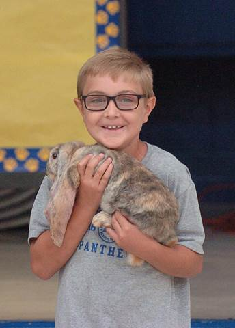 Everett third grader Sawyer Brooks smiles after being shown how to hold an English Lop rabbit.
