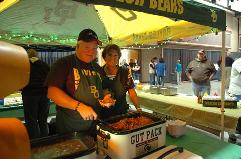 Under the Baylor Bears tent, Stephen 'Red' Holmes and JoNel Eads serve the popular 'Gut Packs' to tailgaters at the NLEF Tailgate Party.