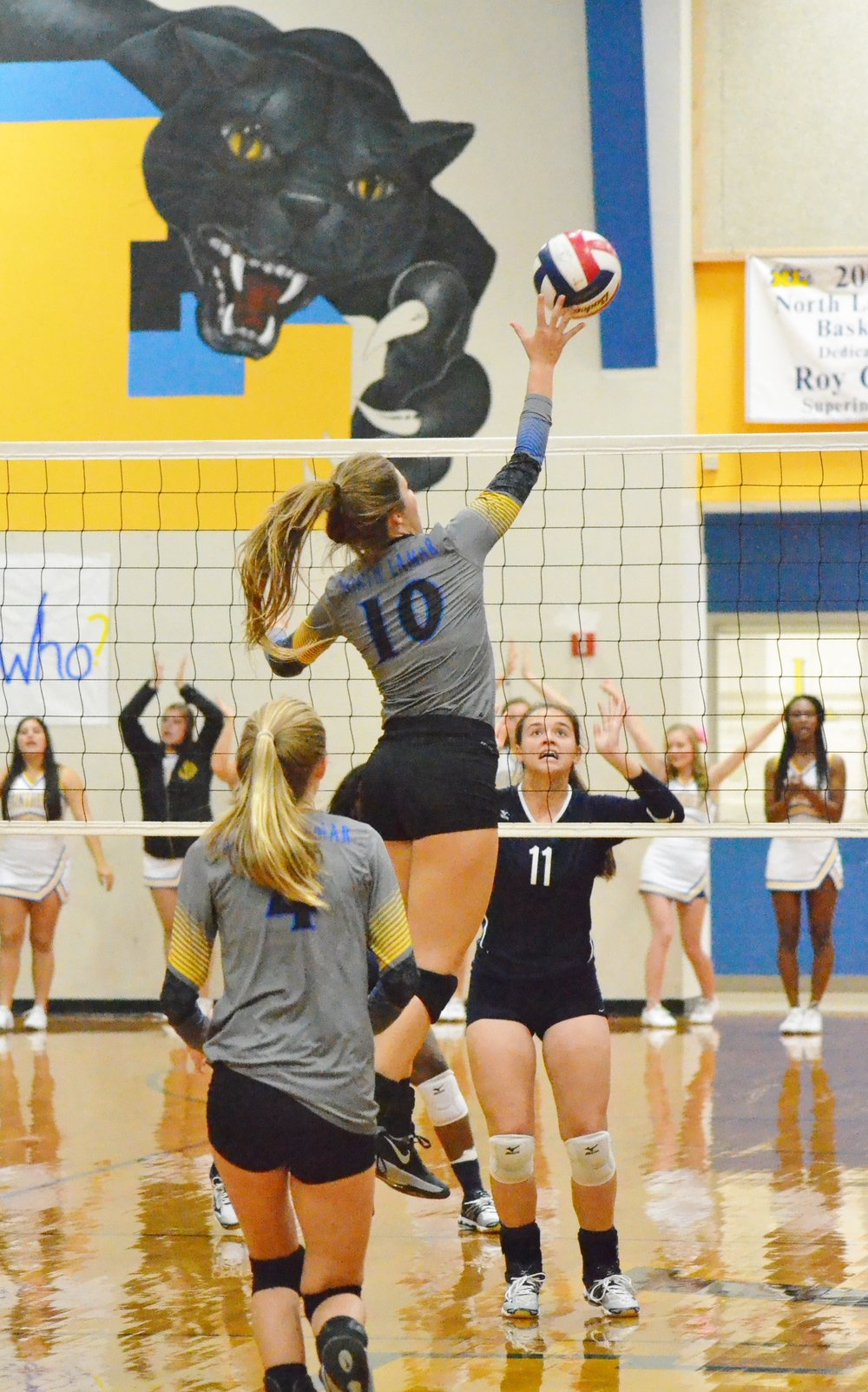 (Photo by Beverly White) Bailee Nickerson (10) hits the ball over while Karlie Ewell (4) watches.
