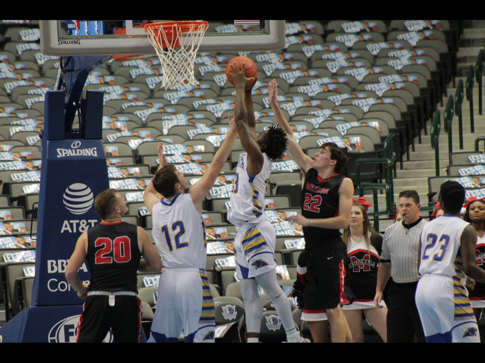Menderiz Gray securing a rebound for North Lamar with Jake Stewart (12) and  TK Finch (23) also there for North Lamar.