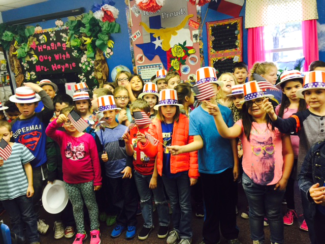 Jennifer Haynie's second grade students at Everett Elementary wear red, white and blue hats and wave flags while FaceTiming Everett teacher Taylor Bland.  Bland left Wednesday evening to attend the week's activities in Washington D.C.