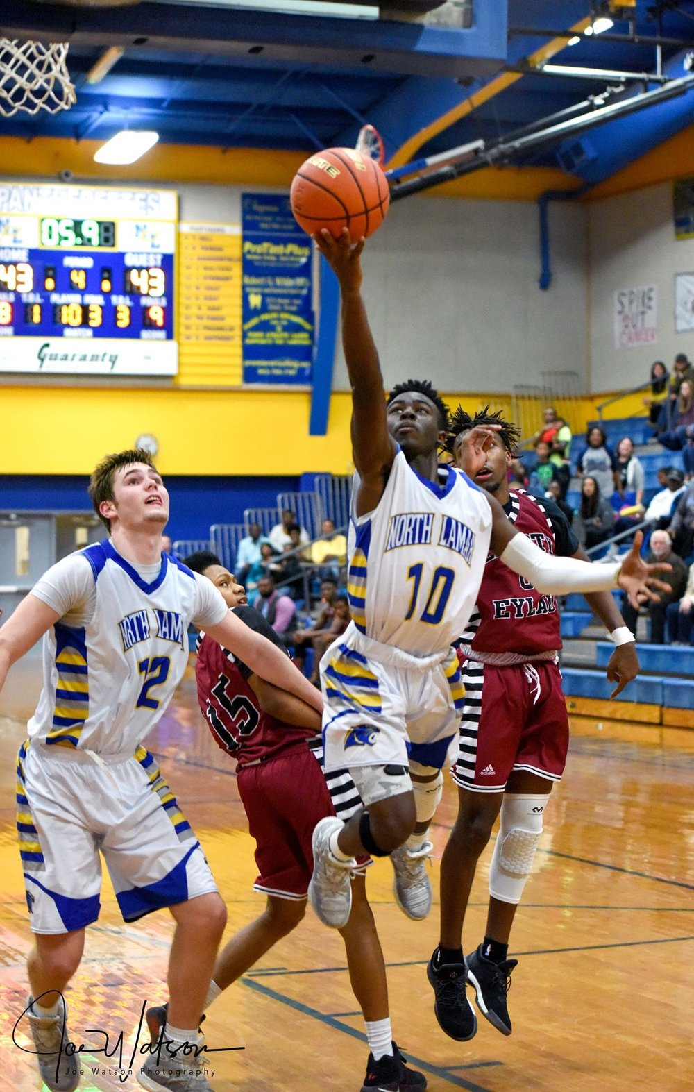 (Photo by Joe Watson) Jay Walters (10) with a layup to win the game for North Lamar as Jake Stewart (12) watches.