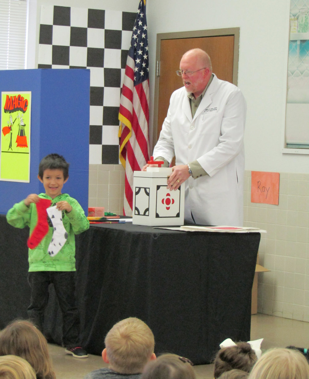 Higgins Elementary kindergarten studentMason Montezassists Dr. Robert White with a magic trick.