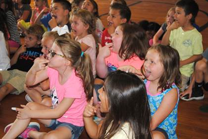First grade students at Aaron Parker Elementary use their fingers to practice brushing their teeth as they watch a demonstration from the school nurse.
