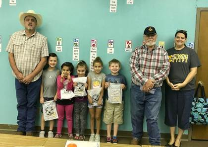 Roan Oak Masonic Lodge members Paul Green, left, and Mike Parson, second from right, stand with first grade teacher Yolanda Lasenbbyand a few of her students who received Fantastic Teeth Fan Club packets. Students beginning left are Manning Fuller, Richelle Kelp-Torres, Emma Pedersen, Cate Emeyabbi, Christopher Rowland,