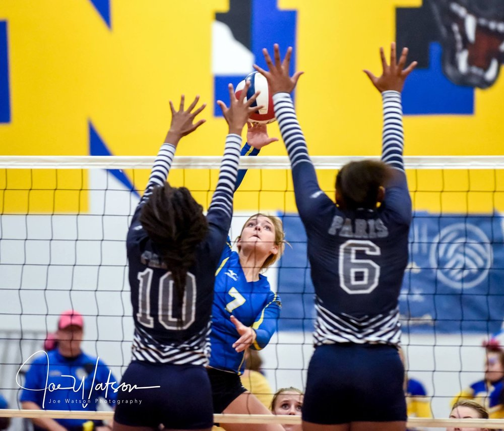 (Photo by Joe Watson) Emma Stewart (7) goes up for a kill against Paris as Zanesha Dangefield (10) and Kiaunsha Jackson (6) attempt a block.