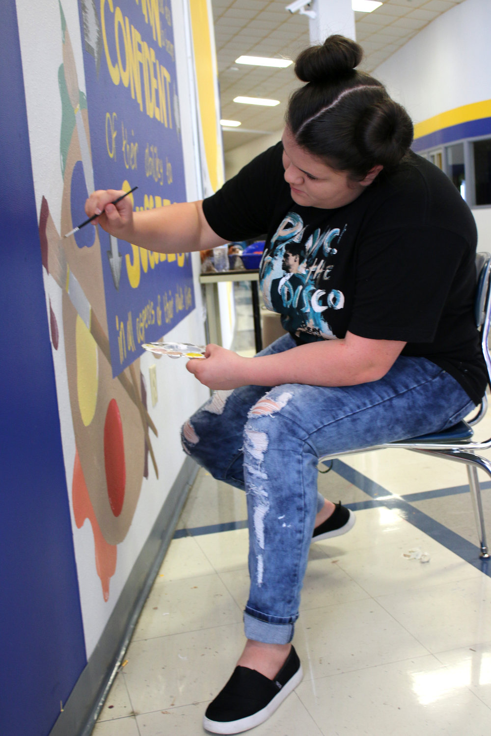 NLHS senior and Art Club president Kareagin Allison puts the finishing touches on the mural that is now displayed in the high school foyer.