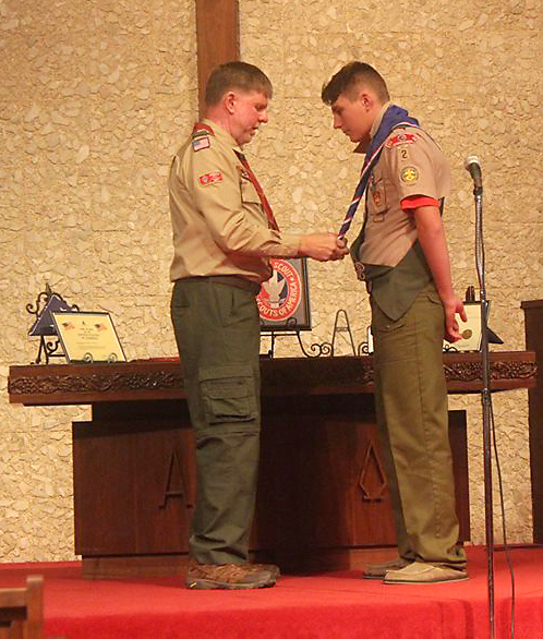 During an Eagle Court of Honor ceremony, Scoutmaster Mike Taylor, left, presents  Justin Daughtrey  the highest achievement in the Boy Scouting program, the Eagle Scout Award.