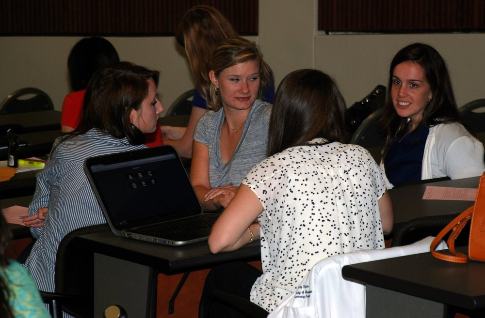 "Students discussing which answer to choose during the ""team test"". The team-based learning model lends itself well to the use of lecture halls.   Students are assigned to sit with their teammates.   During the team portions of the class, the students merely turn in their seats to interact with each other.   The animation of the choice ""turning over"" was set to be slow enough that there is a bit of suspense as the student waited to see if they got a ""check"" or an ""X""."
