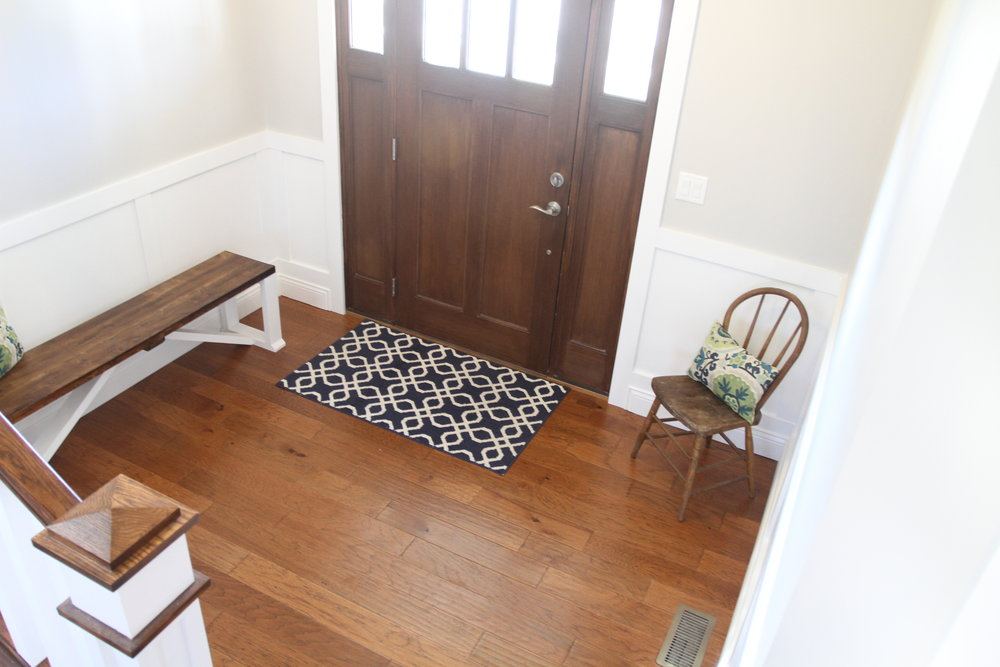 Open front entryway with farmhouse bench and chair