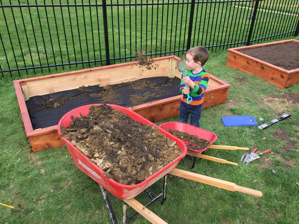 My little assistant helping me fill the garden box with dirt